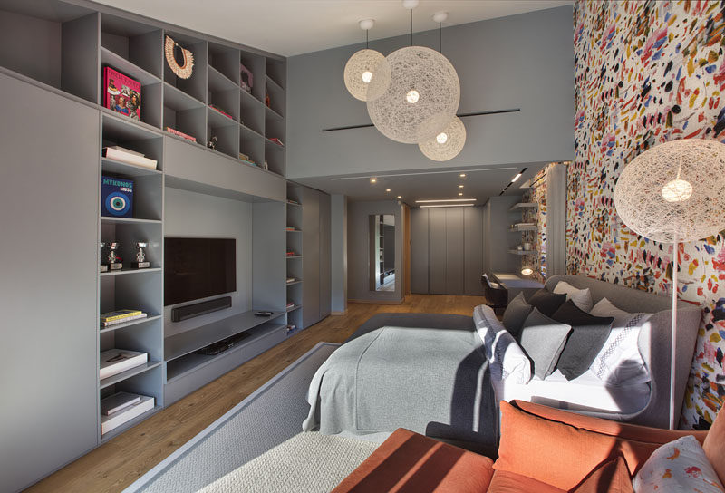 In this modern bedroom, there's a bright and colorful accent wall behind the bed and desk area, while on the opposite wall, built-in shelving and closets create plenty of storage. #ModernBedroom #BedroomDesign #Shelving
