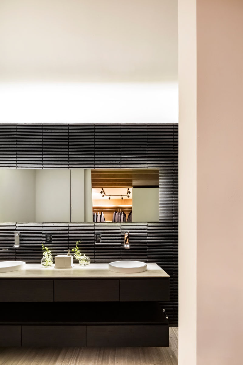 In this modern master bathroom, a black accent wall strongly contrasts the white ceiling, while a blacklit mirror helps to highlight the wall detail and the vanity. #ModernBathroom #BlackBathroom #BacklitMirror