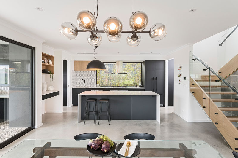 In this modern kitchen, white countertops have been paired with black cabinetry and accessories for a sleek and modern appearance. #ModernKitchen #KitchenDesign #BlackAndWhiteKitchen