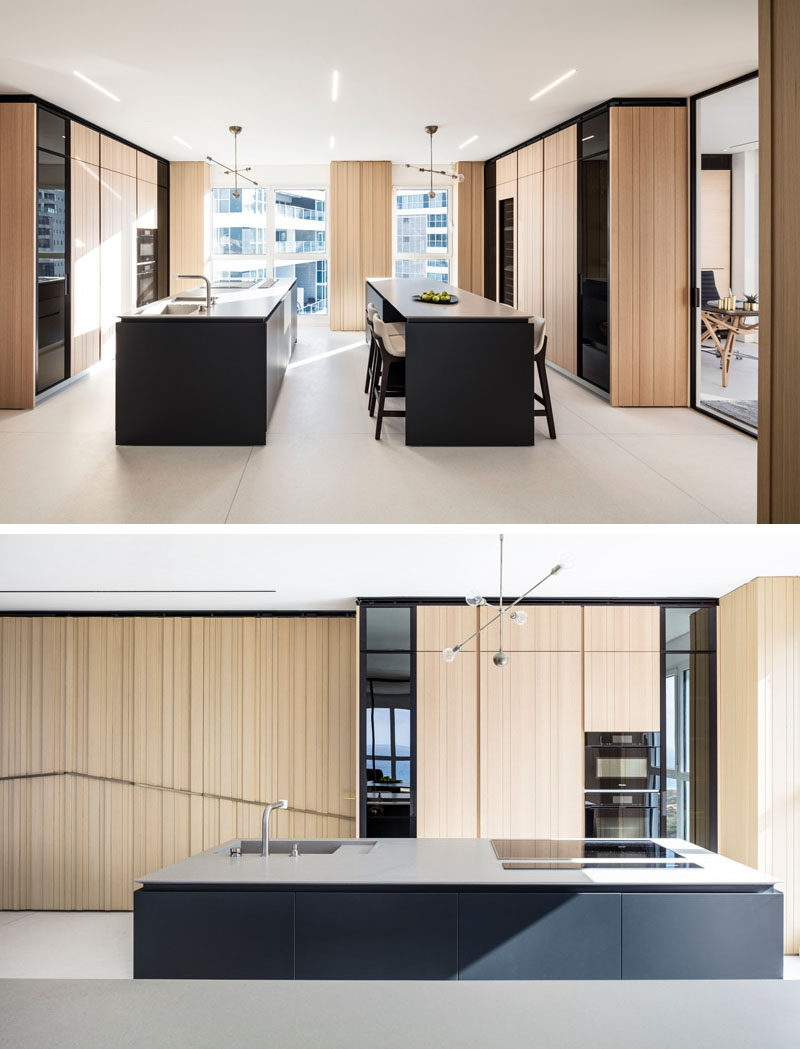 This modern kitchen uses the same wood on the cabinets that's featured on the walls. Two black islands with white countertops create a contrast to the light wood. #ModernKitchen #WoodKitchen #BlackKitchenIsland #KitchenDesign