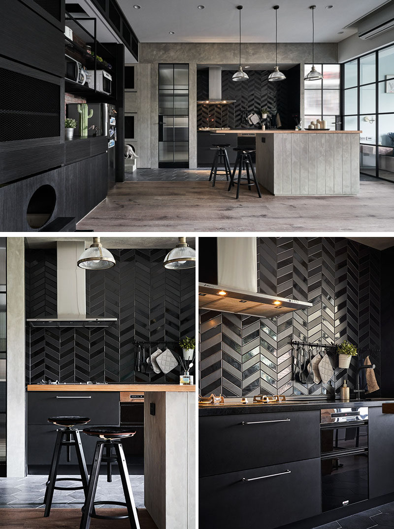 In this modern kitchen, matte and gloss black tiles have been laid in a chevron pattern, while the lower cabinets are also black. #ModernKitchen #BlackTiles #KitchenDesign