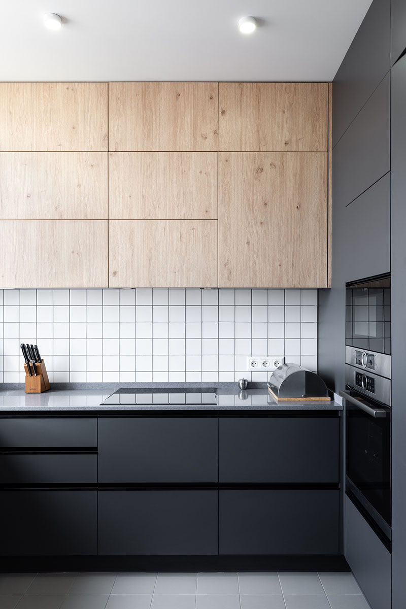 In this modern kitchen, black cabinetry contrasts the white tiles, while upper wood cabinets add a natural touch. #ModernKitchen #BlackCabinets #KitchenDesign