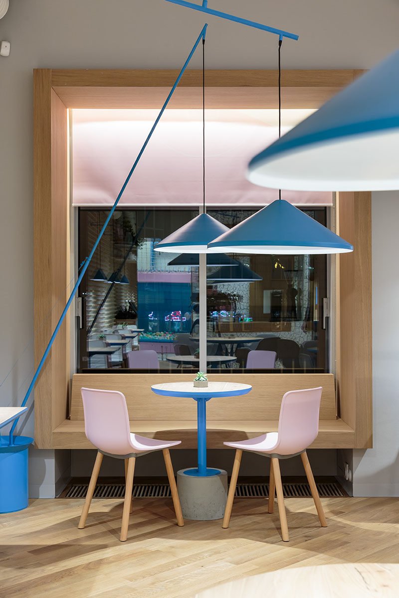 In this modern cafe, the windows have been framed in wood that doubles as a banquette for multiple people to sit at. #Cafe #CafeDesign #Windows #InteriorDesign