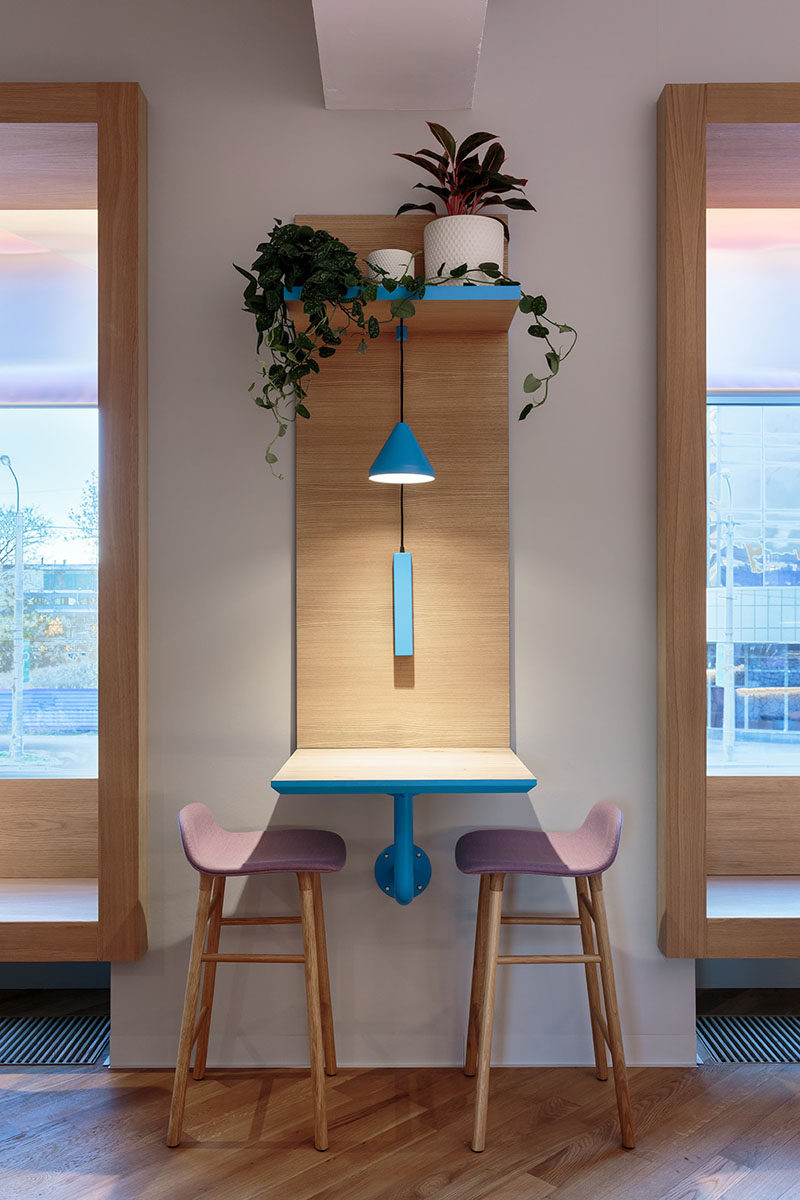 This modern cafe has sections of wood that flow from the walls and transform into tables. They also have a platform to hold plants and to hang the lighting from. #Cafe #CafeDesign #InteriorDesign