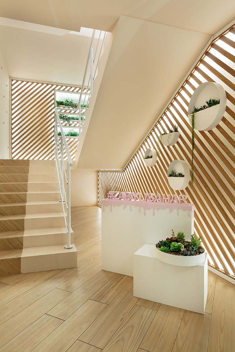 Upon arrival at this modern cafe, stairs with walls of back-lit diagonal wood slats and planters lead upstairs. #Stairs #AccentWall #InteriorDesign