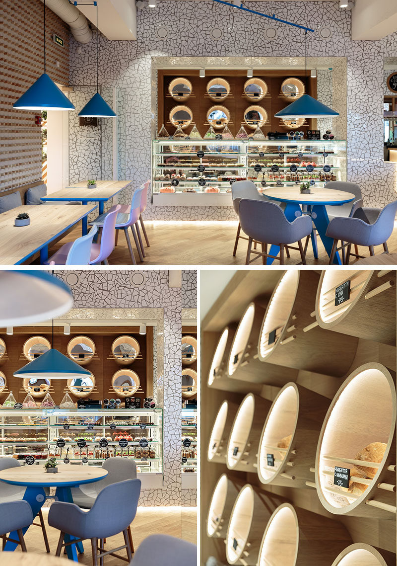 In this modern cafe, chipped white tiles have been installed on the wall surrounding the service area, and deep custom wood circles with mirrors and hidden lighting hold the various items for sale. #Cafe #CafeDesign #InteriorDesign #RetailDesign