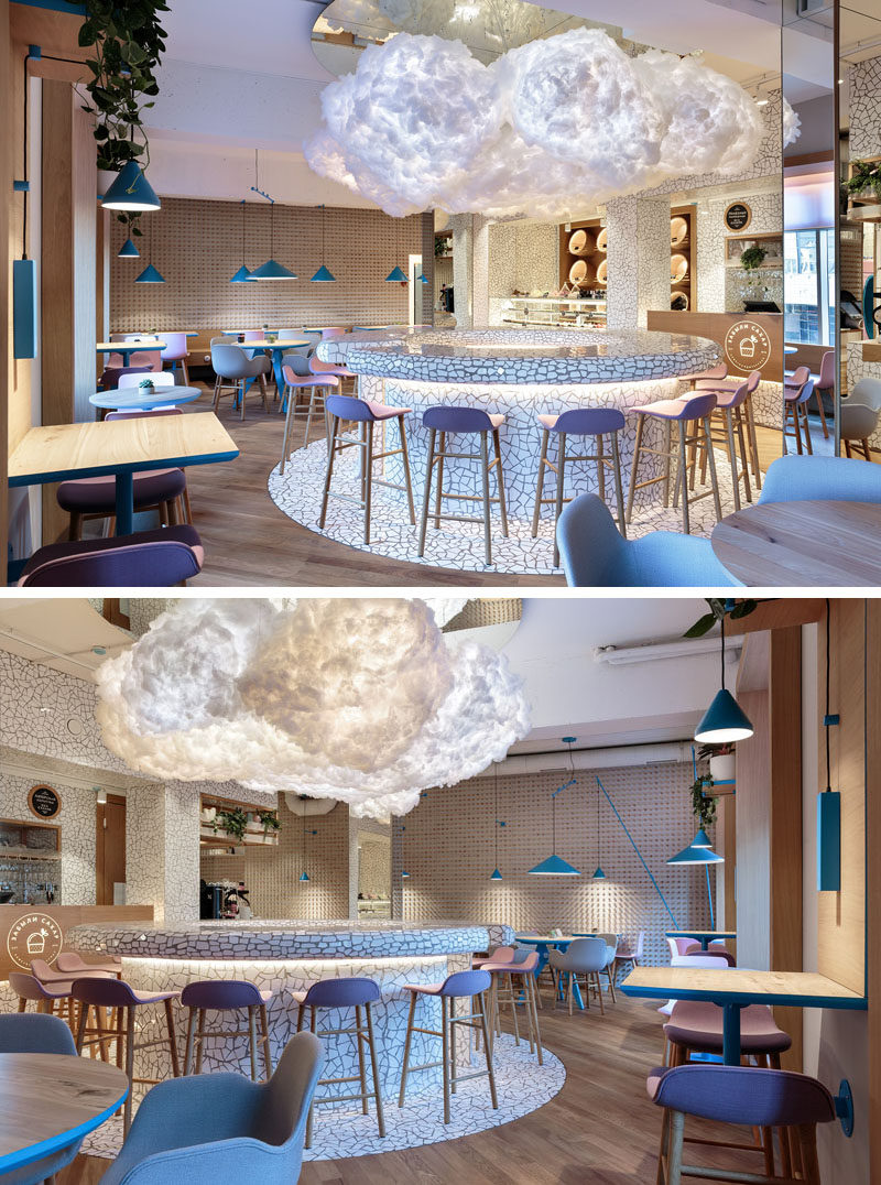 A large cloud light hangs in the middle of this modern cafe above a circular bar area, that features a white chipped tile surface. #Cafe #CafeDesign #InteriorDesign #CloudLight