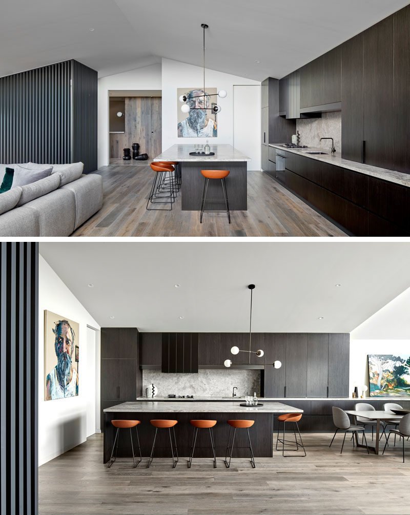 The entryway of this modern house opens up to a large great room, with the kitchen and dining room along one side, and the living room on the other. Dark wood cabinets have been paired with light countertops in the kitchen. #ModernKitchen #KitchenDesign #DarkWoodKitchen