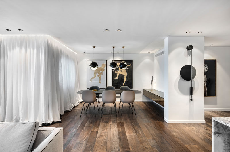 This modern apartment has a dining area anchored by three pendant lights, while a white curtain warps around the interior to provide privacy when needed. #DiningRoom #WoodFloors #Curtain