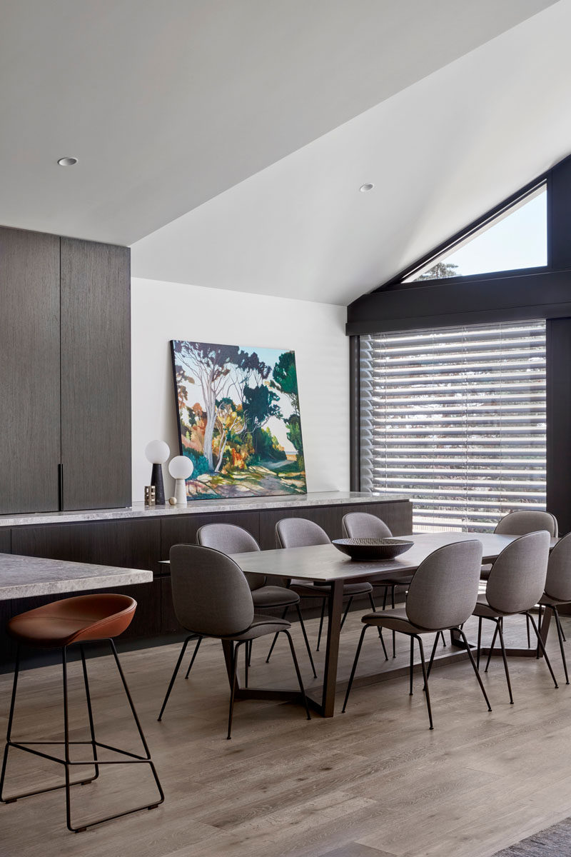 The counter and lower cabinets of the kitchen continuing through to this modern dining area, acting as a sideboard. #DiningArea #DiningRoom