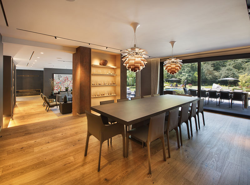 This modern dining room has a large dining table, built-in display shelves, and a large sliding glass door that opens up to an outdoor dining patio. #DiningRoom #ModernDiningRoom