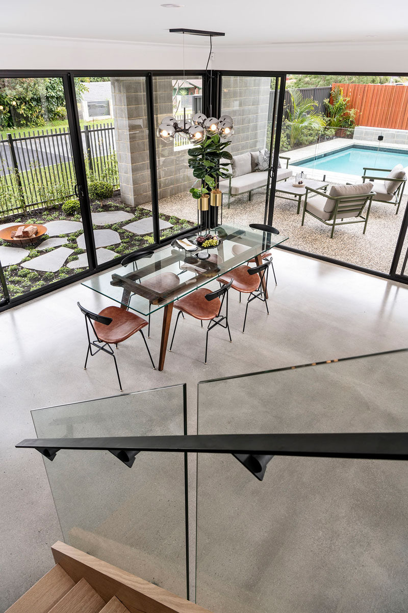 Walls of glass with sliding doors open to connect the interior and exterior living spaces of this modern house. The dining room features a glass dining table with a chandelier hanging above. #ModernHouse #ConcreteFloors #DiningRoom #OutdoorSpaces #GlassWalls
