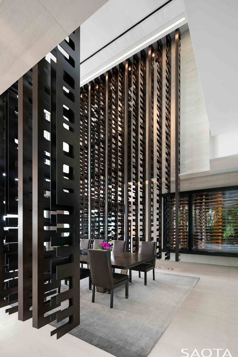 This modern house has a series of bronze screens which hang from the ceiling, creating a double height formal dining room. #ModernDiningRoom #RoomPartition #RoomDivider #Screen