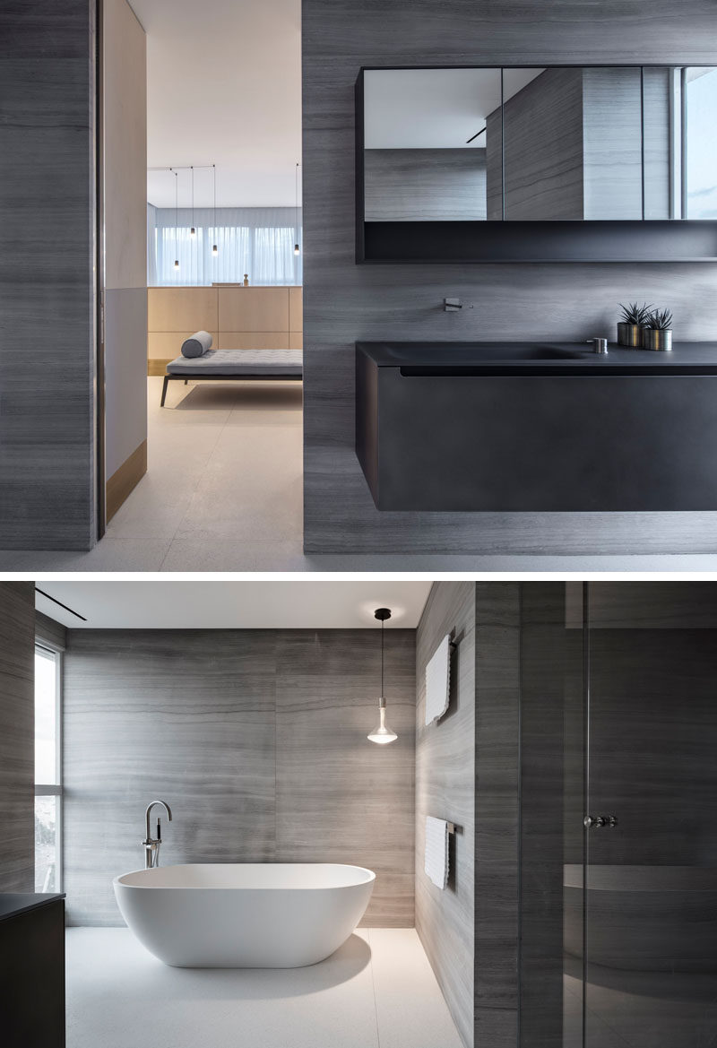 This modern ensuite bathroom has grey walls, a dark metal vanity, and a freestanding white bathtub. #ModernBathroom #EnsuiteBathroom #BathroomDesign