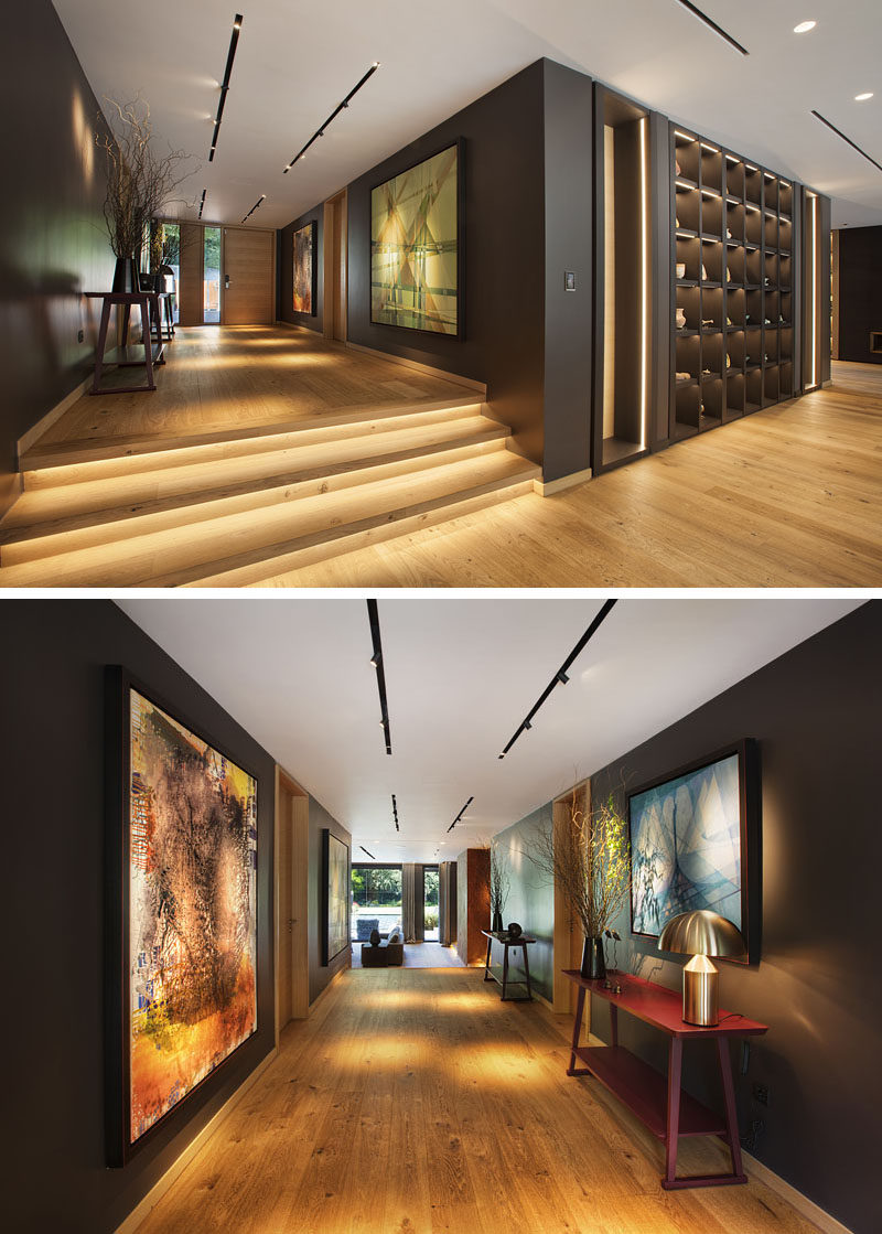 Inside this modern house, wood has been used to create a warm and inviting living space. In the entryway hallway, dark walls contrast the wood flooring, while track lighting highlights artwork. #Entryway #Hallway #Steps