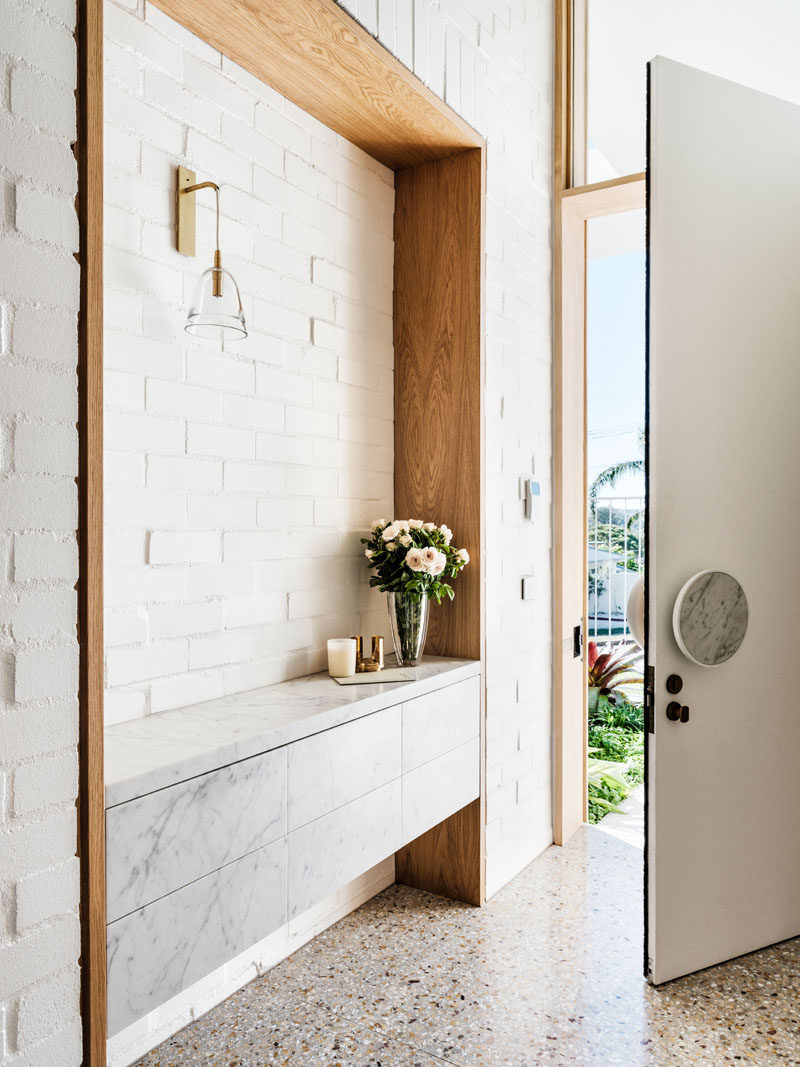Inside the front door of this modern house, there's a built-in wood framed sideboard in the entryway, while a white brick wall adds texture to the space. #Entryway #ModernInteriorDesign