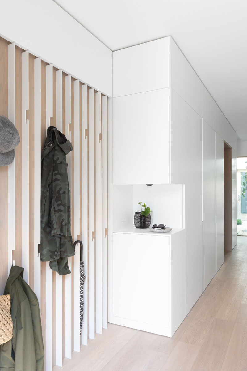 This modern entryway features a wall of bespoke slatted steel coat hook, and a small open shelf cut out in the white cabinetry. #ModernEntryway #InteriorDesign
