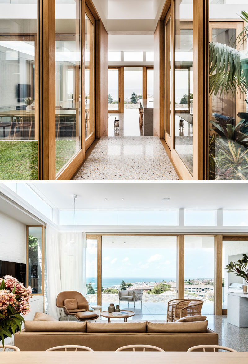 Wood-framed sliding glass doors open both the hallway and modern living room to different outdoor areas. #SlidingGlassDoors #LivingRoom #Hallway