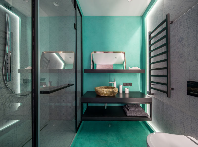 In this modern bathroom, bright turquoise on the floor and wall adds a pop of color, while the walk-in shower and opposite wall both have the same decorative tile. #ModernBathrooom #BathroomDesign