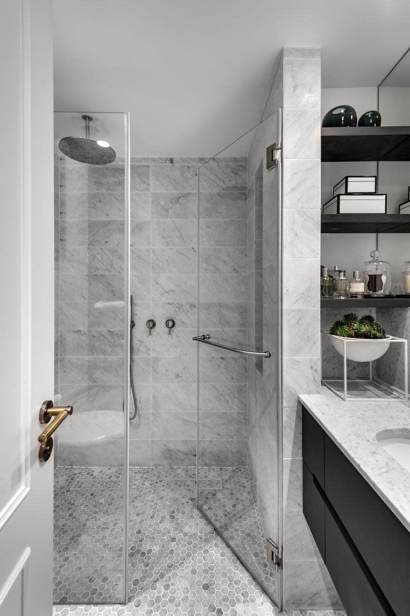 This modern bathroom design with a glass enclosed shower, has a simple grey, black and white color palette. #BathroomDesign #ModernBathroom