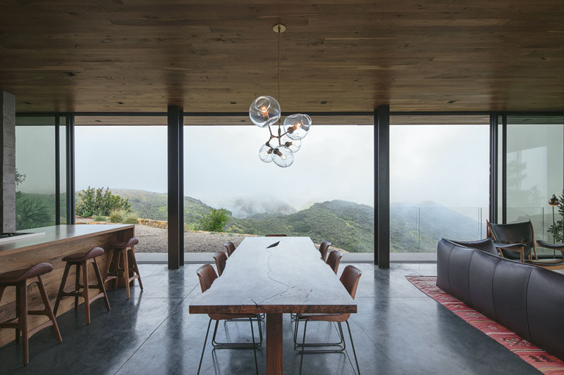This modern guest house has sliding glass walls that open up the dining area to a balcony and outdoor space. #DiningRoom #GlassWalls #InteriorDesign
