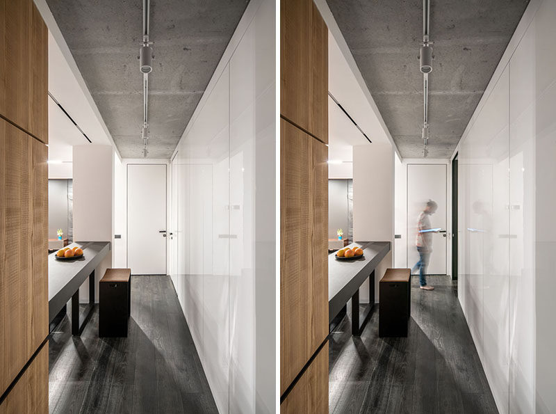 A hidden door within a wall of glossy white cabinets provides access to the other areas of this modern apartment. #WhiteCabinets #HiddenDoor