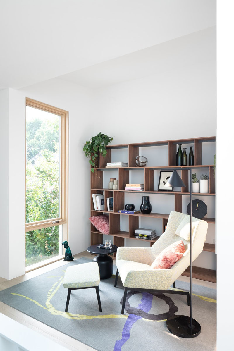 This modern house has a small den / home library space with a comfortable chair, wood shelving, and view outside. #HomeLibrary #Den #InteriorDesign