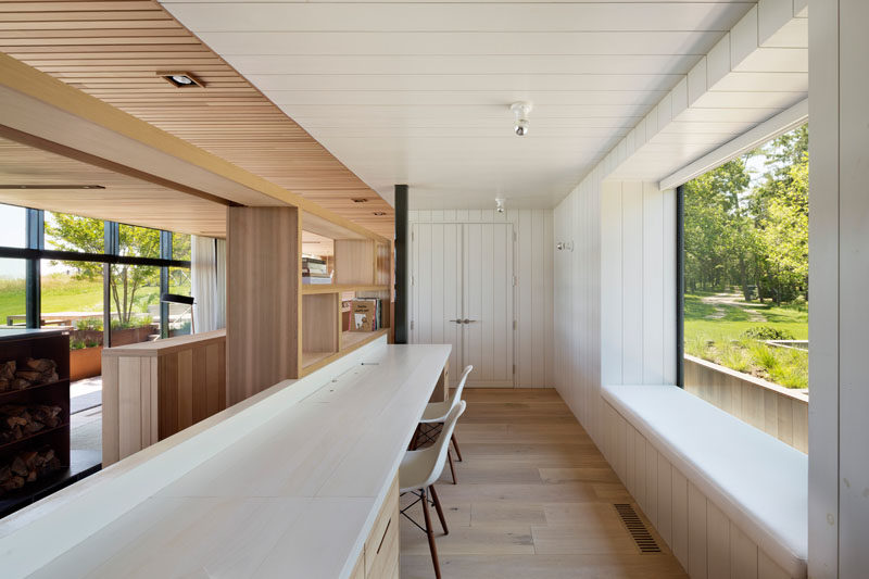 This modern home office with a long desk, overlooks the living room, while a window seat looks out towards the front garden. #HomeOffice #WindowSeat #LongDesk
