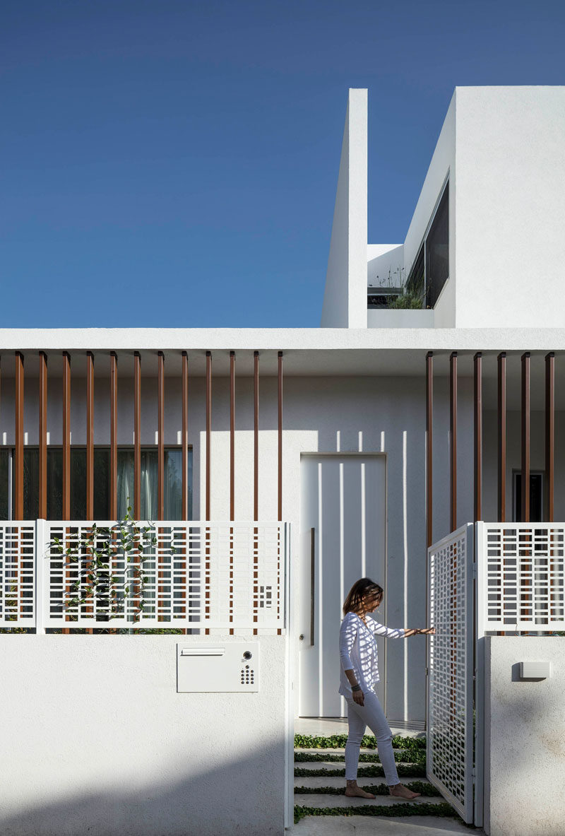 A white gate with a decorative pattern welcomes visitors to this modern house. #Gate #Architecture #ModernGate