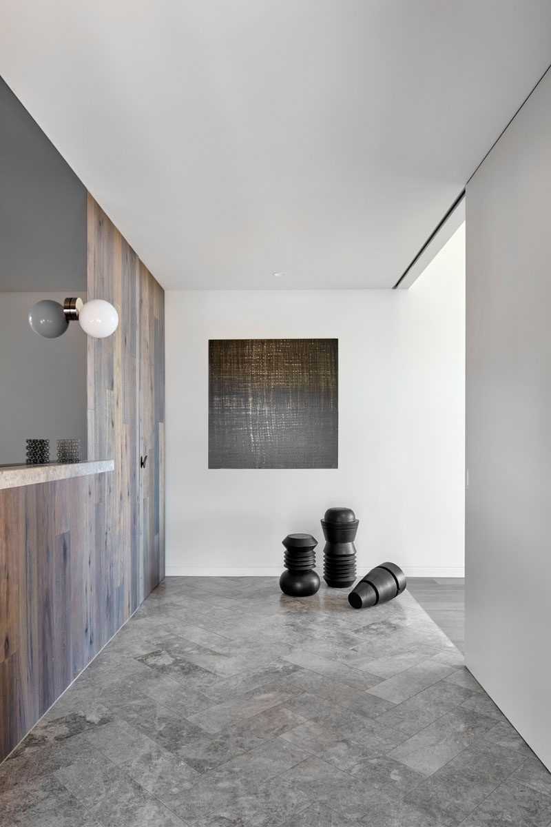 The entryway of this modern house features flooring laid in a herringbone pattern. #ModernEntryway #HerringbonePattern #Flooring