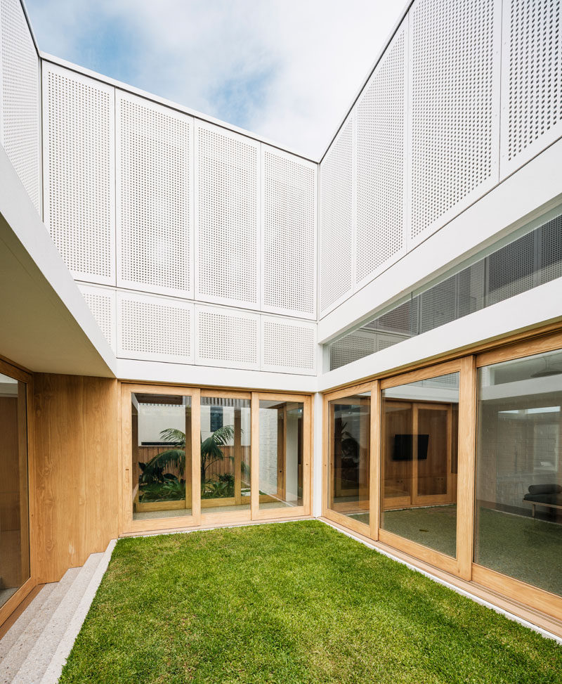 The interiors of this modern house opens up to an internal grassy courtyard. #Courtyard #ModernArchitecture