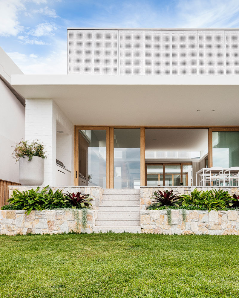 As this modern house is on a sloped site, sandstone planters on either side of the stairs have been included in the landscape design, separating the outdoor dining area and the grassy area below. #Landscaping #Sandstone #ModernHouse