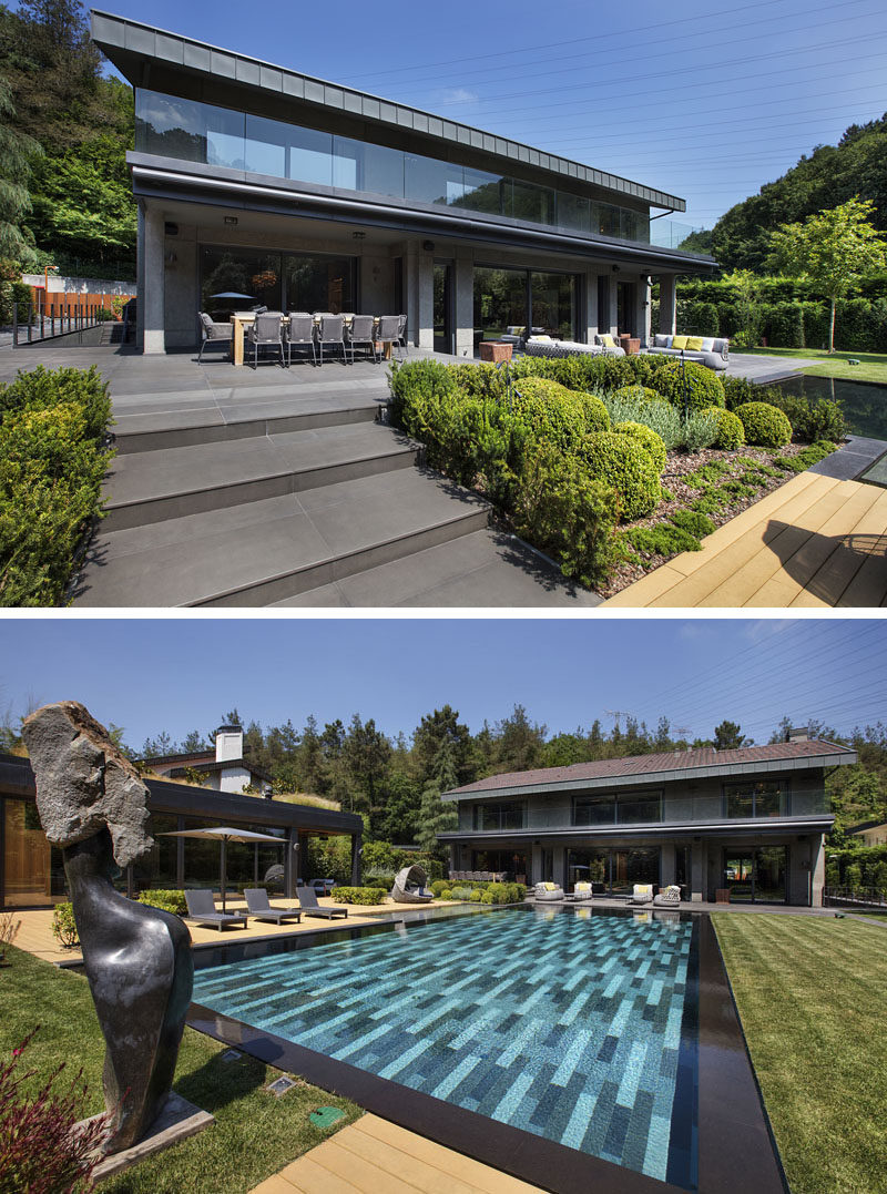 This modern house has an outdoor dining area and outdoor living room that both look out over the swimming pool, backyard and pool house. #ModernHouse #SwimmingPool #OutdoorDining #OutdoorLivingRoom #Landscaping