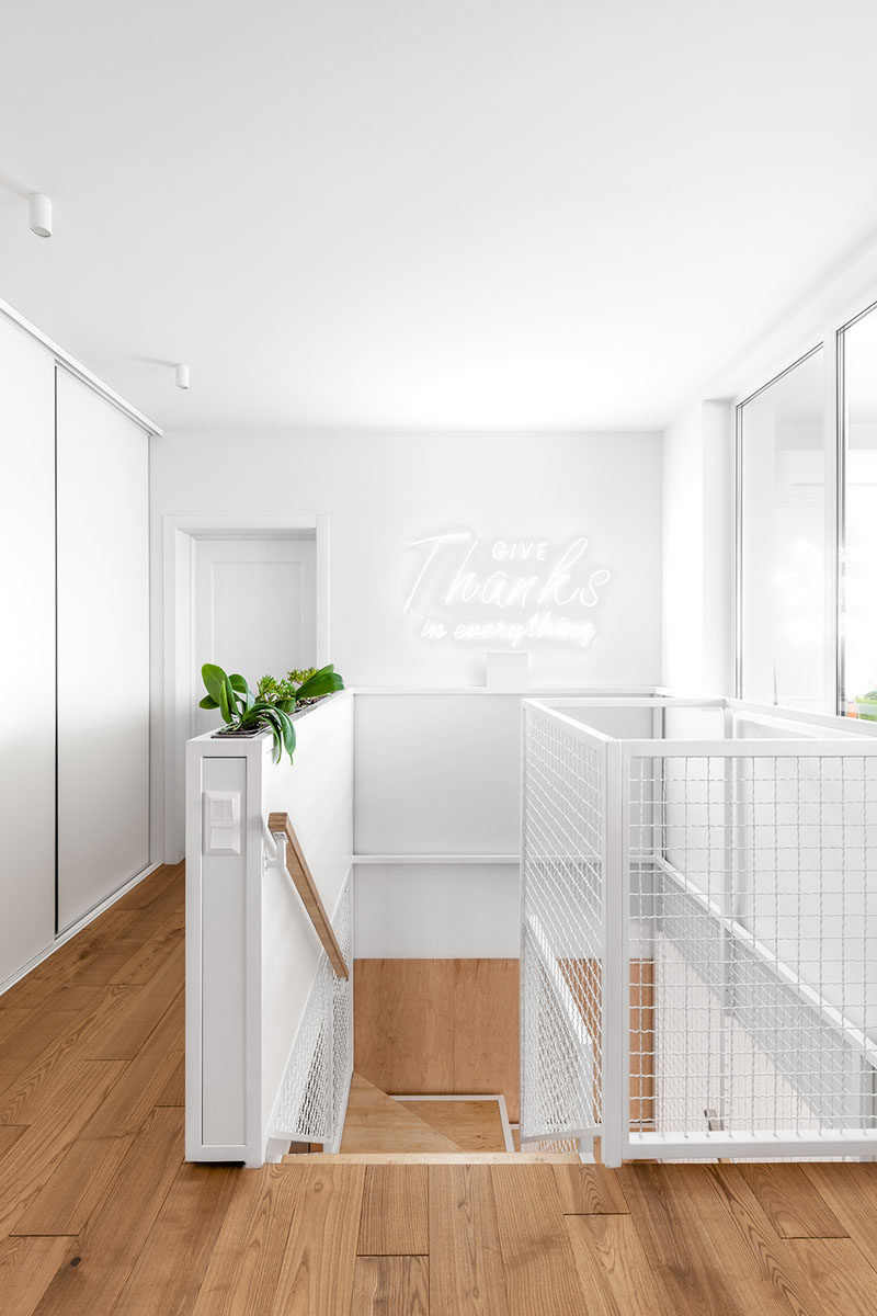 At the top of these modern wood stairs, there's a pony wall with built-in planters, and white walls help to reflect the light coming in from the window. #InteriorDesign #Planters