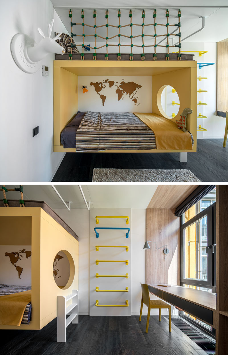 In this modern kids bedroom, the bed is surrounded by a yellow frame with a circular cutout that looks towards the window. A ladder on the wall leads up to a a reading nook above the bed, while against the window, a custom designed desk sits within a wood frame. #ModernKidsBedroom #KidsBedroom #ChildsBedroom