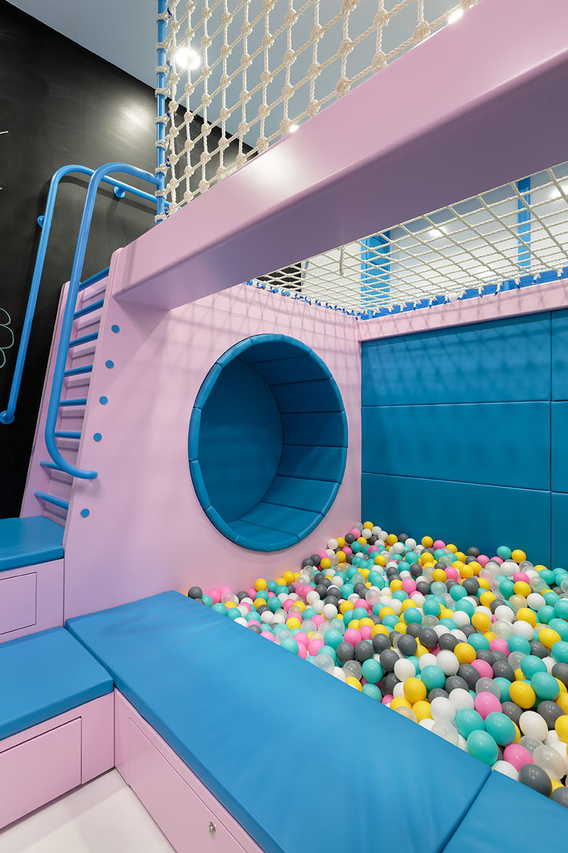 This modern kids play area with a ball pit, seating nook, a chalkboard wall, and a ladder that leads to a net for relaxing in. #KidsPlayArea #BallPit