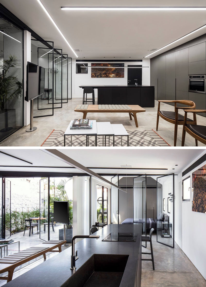 The black island in the kitchen was designed to create a focal point in this modern interior that has polished concrete floors. #ModernKitchen #BlackIsland #ConcreteFloors