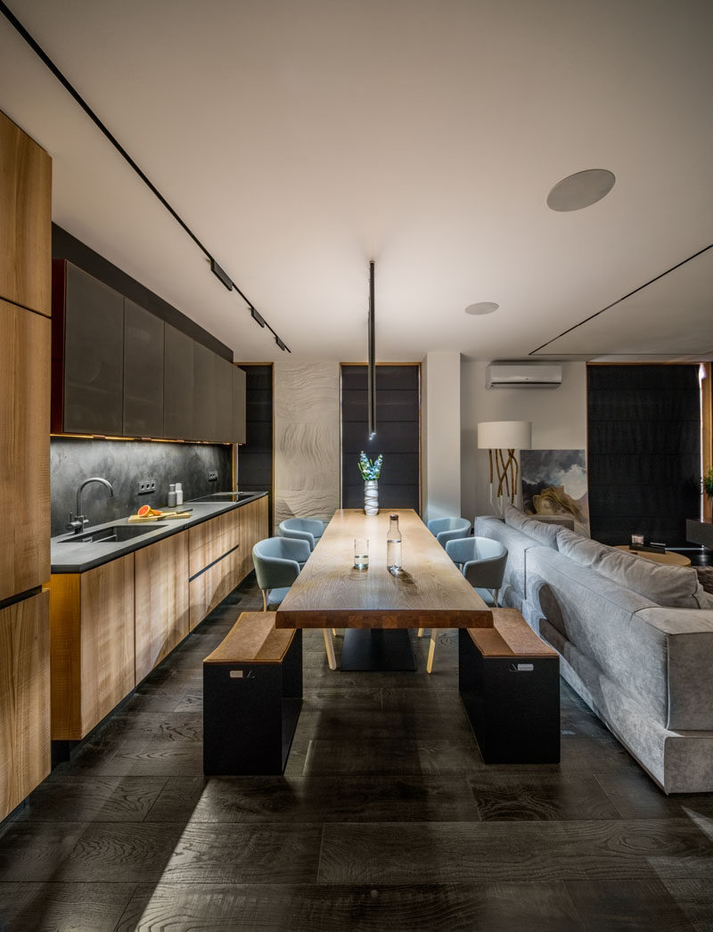In this modern kitchen, a wood table surrounded by seating creates a place for food prep and family meals, while wood and copper kitchen cabinets run along the wall. #DiningRoom #Kitchen #ModernKitchen #InteriorDesign