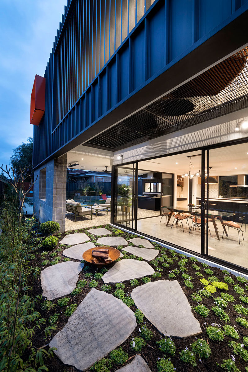 This modern house has a side garden with a small firebowl, that can be accessed from the covered outdoor lounge, or the dining room inside. #SideGarden #Firebowl #ModernHouse #Landscaping