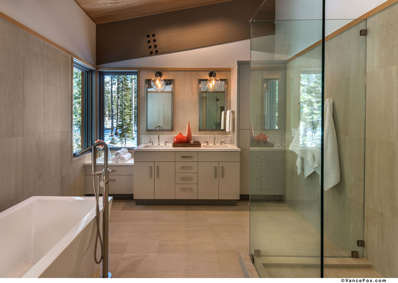 This modern master bathroom has a stand-alone soaking tub, a glass shower surround and a vanity that runs the length of the wall. #MasterBathroom #ModernBathroom