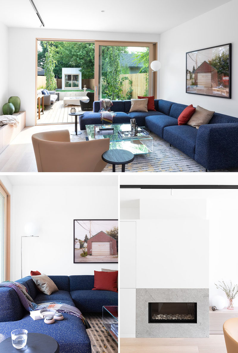 In this modern living room, there's a bright blue couch for a pop of colour, and a flush limestone fireplace. A Lift & Slide door opens the space to patio and garden beyond. #LivingRoom #Fireplace #SlidingGlassDoor