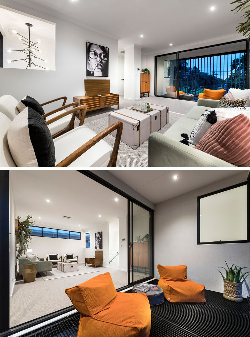 This modern family room opens up to a somewhat enclosed balcony that looks over the street below. #FamilyRoom #LivingRoom #Balcony