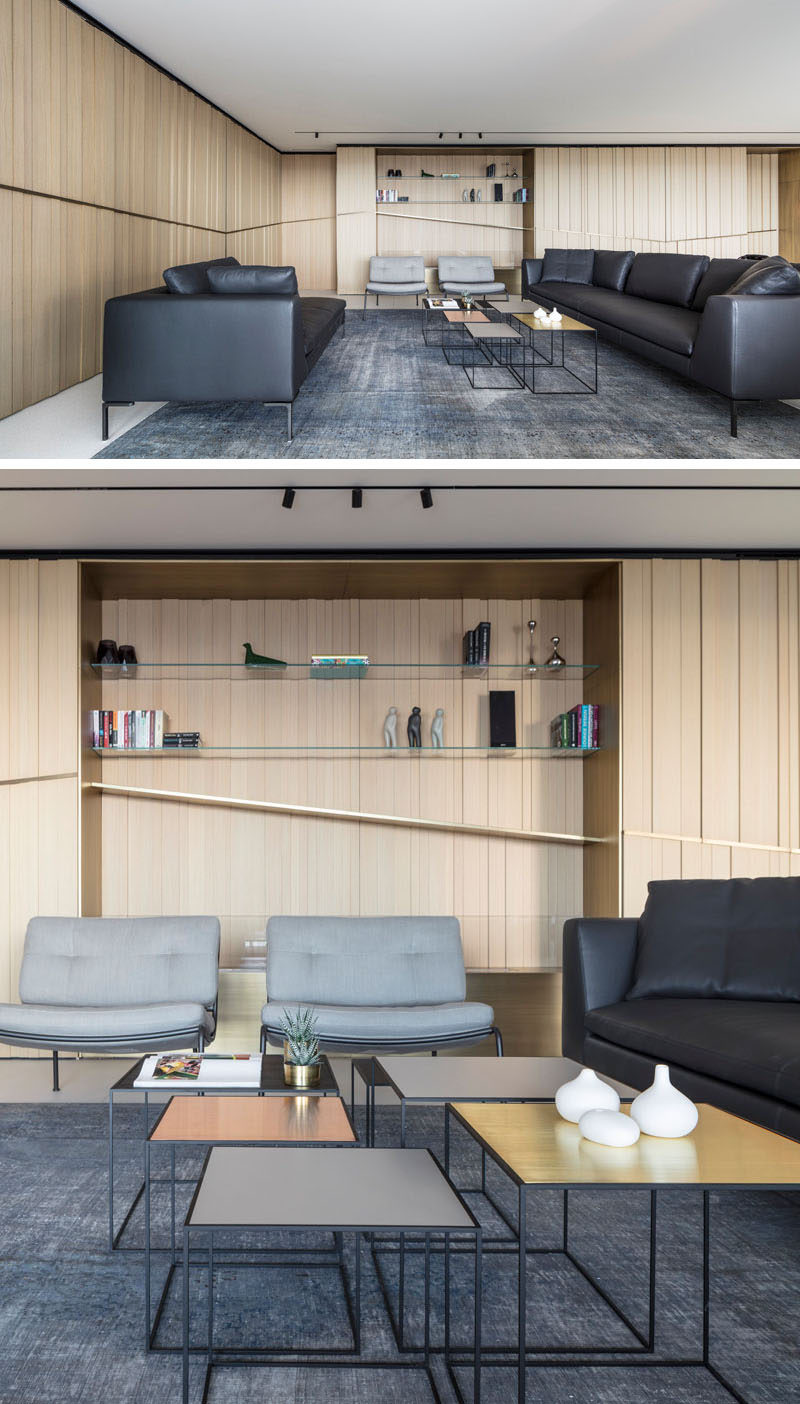The main social areas of this modern apartment are all open plan, with the living room featuring at one end. Built into the wall is an alcove with glass shelves. #LivingRoom #ModernInterior #Shelving #WoodWalls