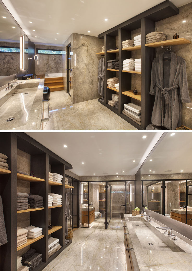 In this modern master bathroom, there's open shelving with places to hang clothes, a long double trough sink, a built-in bath, and a shower with a black-framed glass shower screen. #ModernBathroom #MasterBathroom #BathroomDesign
