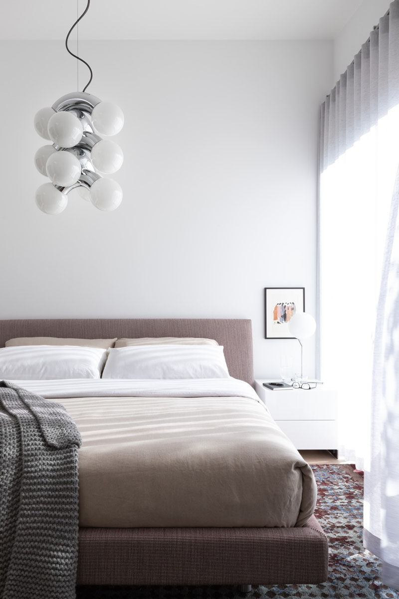 In this modern master bedroom, a neutral color palette creates a calm space, while aAndLight Vine 5 Pendant hangs from the ceiling. #MasterBedroom #ModernBedroom #BedroomDesign