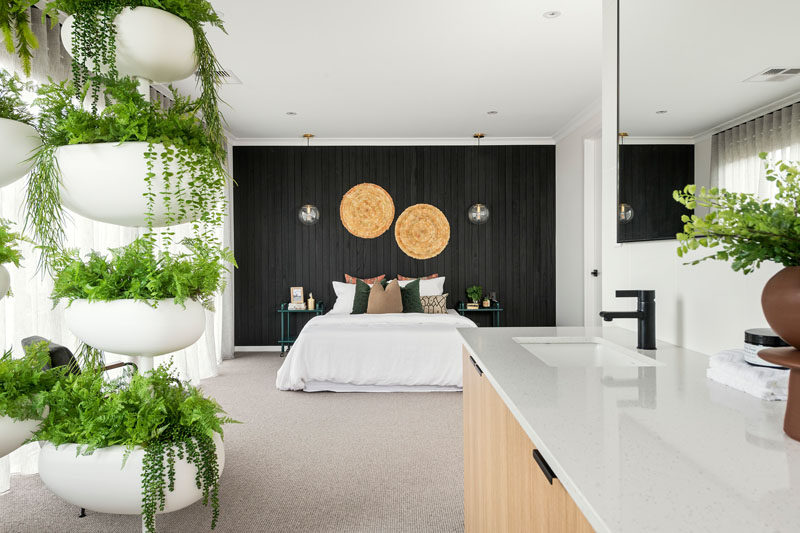 In this modern master bedroom, a black wood accent wall draws the eye to the bed, that looks towards an open ensuite bathroom with a decorative plant stand providing some privacy for the freestanding bathtub. #MasterBedroom #BlackAccentWall #InteriorDesign