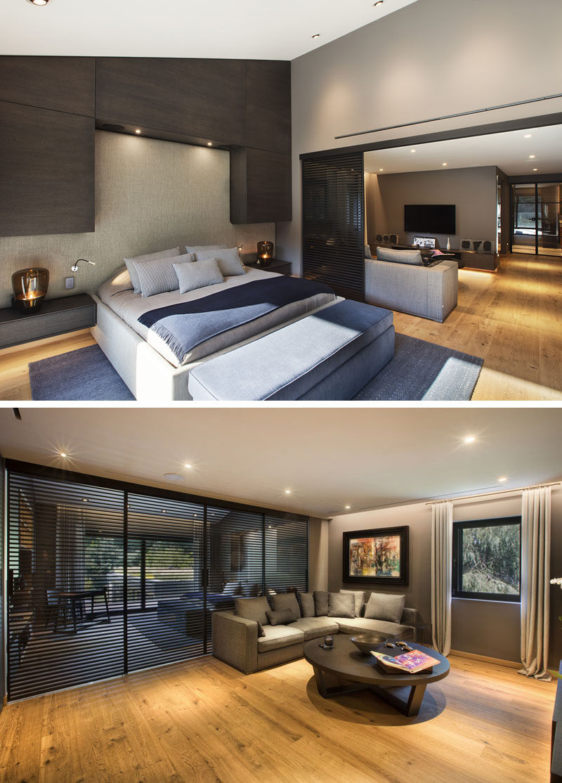 In this master suite, there's the bedroom with built-in dark cabinetry and a sliding screen wall that opens up to a private lounge area. #MasterBedroom #BedroomSuite