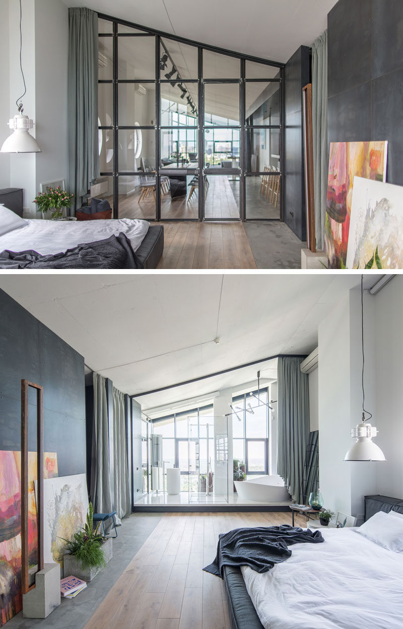 Partitioned off from the social areas of the apartment by a wall of steel-framed glass, is the master bedroom. Steel paneling covers the wall opposite the bed, while the sloped ceiling is accentuated by the glass frames. #MasterBedroom #GlassPanels #EnsuiteBathroom
