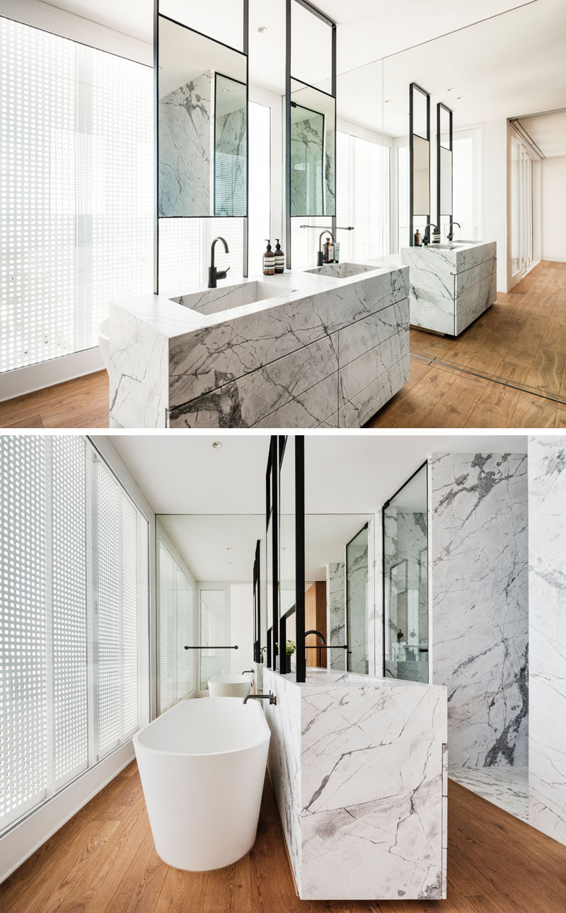In this modern master bathroom, a double sink vanity is positioned in the center of the room, while a freestanding bathtub is located behind the vanity, and a full wall mirror makes the room feel twice as big. #ModernBathroom #BathroomDesign #EnsuiteBathroom