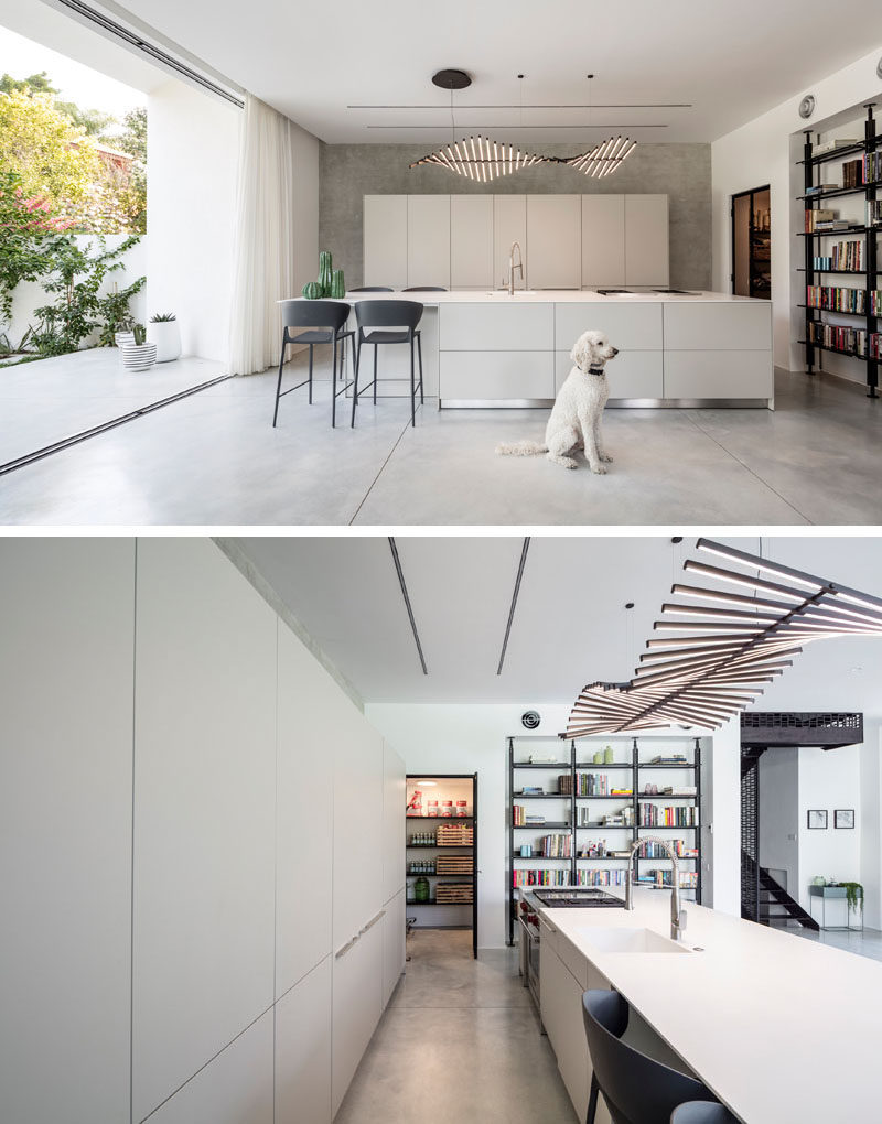 This kitchen has minimalist cabinetry for a sleek and modern look, while a sculptural light fixture hangs above the island. #KitchenDesign #ModernKitchen #MinimalistKitchen